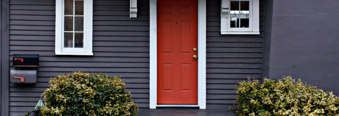 red front door of dark grey house