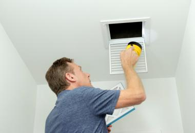 man inside home inspecting a vent