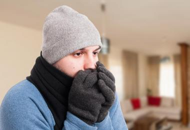 man shivering indoors breathing into grey gloves